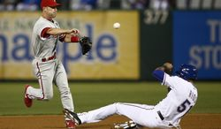 Philadelphia Phillies' Jayson Nix, left, throws to first base turning the first half of a double play on Texas Rangers' Alex Rios (51) during the fourth inning of a baseball game on Wednesday, April 2, 2014, in Arlington, Texas. (AP Photo/Jim Cowsert)