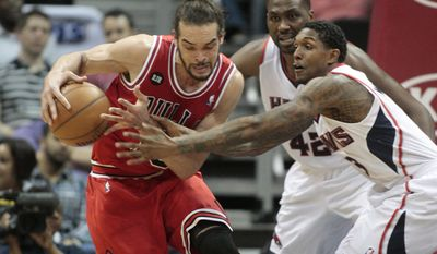 Chicago Bulls center Joakim Noah, left, and Atlanta Hawks guard Lou Williams, right front, scramble for a loose ball as Hawks' Elton Brand watches during the first half of an NBA basketball game Wednesday, April 2, 2014, in Atlanta. (AP Photo/Jason Getz)