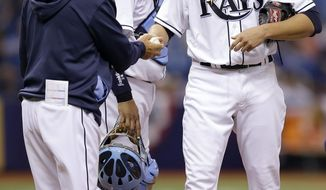 Tampa Bay Rays manager Joe Maddon, left, takes starting pitcher Matt Moore, right, out of the game against the Toronto Blue Jays during the sixth inning of a baseball game Wednesday, April 2, 2014, in St. Petersburg, Fla. Looking on is catcher Jose Molina. (AP Photo/Chris O'Meara)