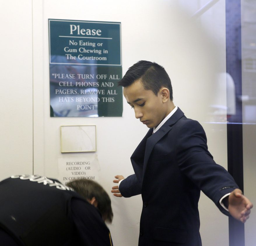 Justin Casquejo passes through security at a courthouse in New York, Wednesday, April 2, 2014. The 16-year-old boy described as a thrill-seeker bypassed an inattentive security guard in the middle of the night and climbed a ladder to the spire of 1 World Trade Center, where he apparently took pictures, authorities said. (AP Photo/Seth Wenig)