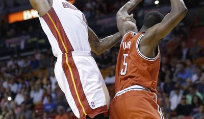 Miami Heat forward LeBron James, left, dunks against Milwaukee Bucks forward Ekpe Udoh (5) during the first half of an NBA basketball game on Wednesday, April 2, 2014, in Miami. (AP Photo/Wilfredo Lee)