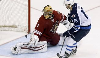 Winnipeg Jets' Andrew Ladd (16) scores against Phoenix Coyotes' Thomas Greiss (1), of Germany, during a shootout in an NHL hockey game, Tuesday, April 1, 2014, in Glendale, Ariz.  The Jets defeated the Coyotes in a shootout 2-1. (AP Photo/Ross D. Franklin)