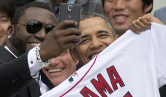 "FILE - In this Tuesday, April 1, 2014, file photo, Boston Red Sox designated hitter David ""Big Papi"" Ortiz takes a selfie with President Barack Obama, holding a Boston Red Sox jersey presented to him, during a ceremony on the South Lawn of the White House in Washington, where the president honored the 2013 World Series baseball champion Boston Red Sox. Ortiz tweeted the selfie to his followers Tuesday, and it was resent by tens of thousands, including Samsung, which retweeted it as an ad. The White House press secretary says Obama was not aware that the photo was part of a marketing stunt. (AP Photo/Carolyn Kaster, File)"