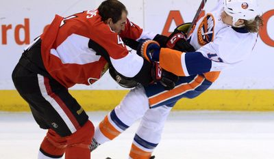 Ottawa Senators' Chris Phillips, left, hits New York Islanders' Matt Martin during the second period of an NHL hockey game in Ottawa, Ontario, on Wednesday, April 2, 2014. (AP Photo/The Canadian Press, Sean Kilpatrick)