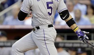 Colorado Rockies' Carlos Gonzalez follows through on an RBI-double to score Michael Cuddyer in the first inning of a baseball game against the Miami Marlins, Wednesday, April 2, 2014, in Miami. (AP Photo/Lynne Sladky)