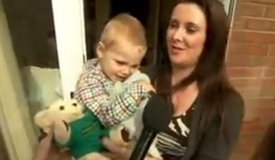 Dana Henry with 2-year-old Riley Ward, who called emergency services when his mother collapsed. (BBC News via YouTube)
