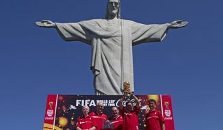 FILE - In this Thursday, Sept. 12, 2013 file photo, Brazil's former World Cup champions, from left, Zagallo, Marcos, Rivellino, Amarildo who holds the World Cup, and Bebeto pose for a photo below the Christ the Redeemer statue at the launch of the FIFA World Cup Trophy Tour in Rio de Janeiro, Brazil. World Cup sponsor Coca-Cola has disclosed contingency plans to soften the celebratory tone of its sponsorship of football's showpiece event in Brazil if unrest returns to the streets. (AP Photo/Silvia Izquierdo, File)