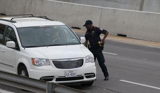 A police officer checks drivers' IDs outside the main gate at Fort Hood, Texas, after a shooting at the Army base Wednesday, April 2, 2014. (AP Photo/Austin American-Statesman, Deborah Cannon) ** FILE **