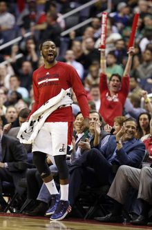Washington Wizards guard John Wall, left, celebrates near the bench during the second half of an NBA basketball game against the Boston Celtics on Wednesday, April 2, 2014 in Washington. The Wizards won 118-92, and clinched a playoff berth. (AP Photo/Alex Brandon)