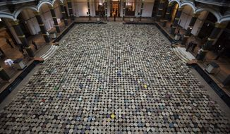 The artwork 'Stools' by Chinese artist  Ai Weiwei is displayed in the atrium of the Martin-Gropius-Bau Museum at the exhibition 'Evidence' in Berlin, Wednesday, April 2, 2014. The museum said with the exhibition 'Evidence' they present the largest  exhibition of Ai Weiwei . The exhibition will be open from April 3 until July 7,  2014. (AP Photo/Markus Schreiber)
