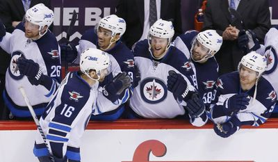 Winnipeg Jets' Andrew Ladd (16) celebrates his shootout goal against the Phoenix Coyotes with teammates Blake Wheeler (26), Evander Kane (9), Matt Halischuk (15), Eric O'Dell (58) and Jim Slater (19) during an NHL hockey game, Tuesday, April 1, 2014, in Glendale, Ariz. The Jets defeated the Coyotes 2-1. (AP Photo/Ross D. Franklin)