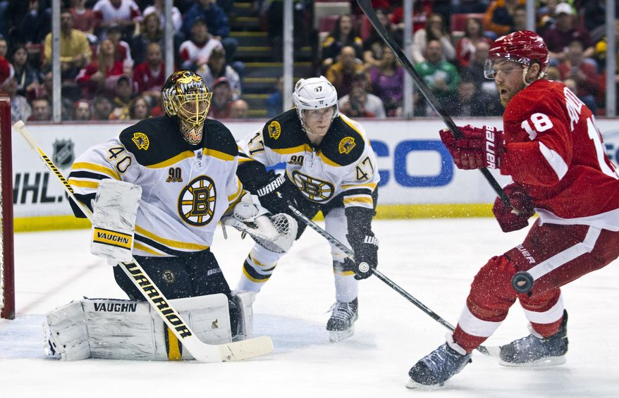 Boston Bruins goalie Tuukka Rask (40), of Finland, and defenseman Torey Krug (47) watch the puck deflect off the left leg of Detroit Red Wings forward Joakim Andersson (18) during the second period of an NHL hockey game in Detroit, Mich., Wednesday, April 2, 2014. (AP Photo/Tony Ding)