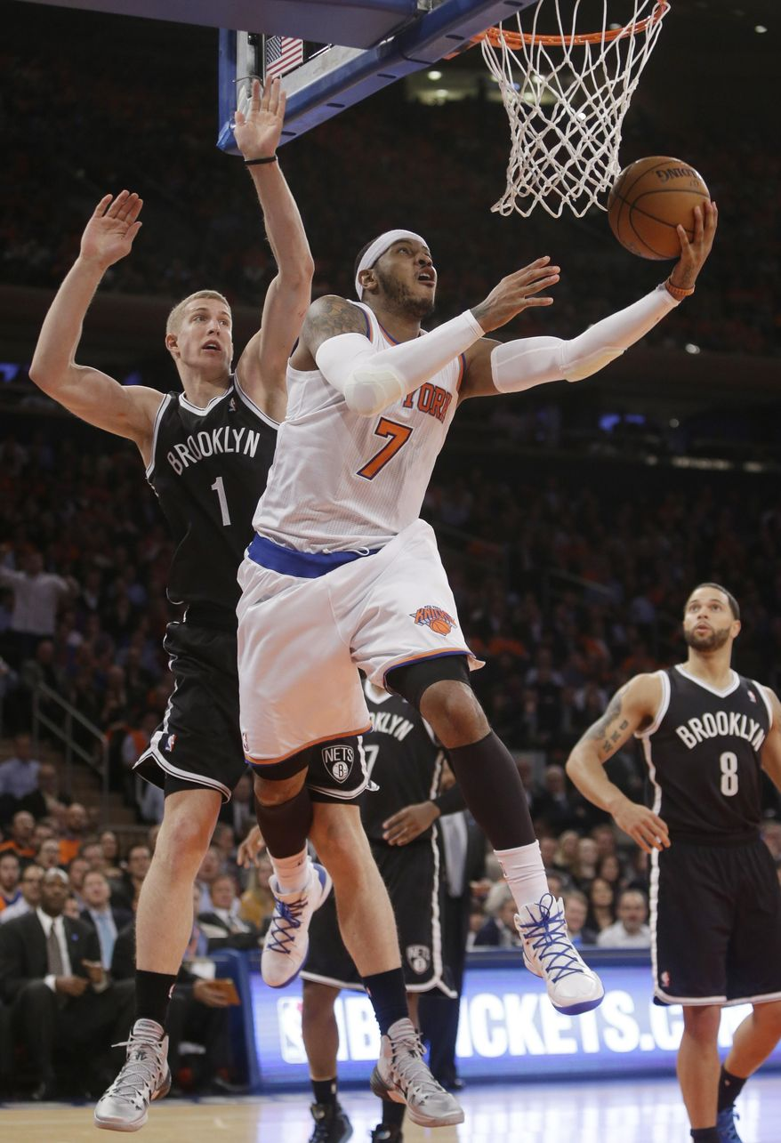 New York Knicks' Carmelo Anthony (7) drives past Brooklyn Nets' Mason Plumlee (1) during the first half of an NBA basketball game Wednesday, April 2, 2014, in New York.  (AP Photo/Frank Franklin II)