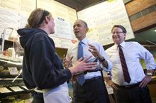 President Barack Obama, accompanied by Rep. Gary Peters, D-Mich., right, talks with employee Andrea Byl to order lunch during their visit to Zingerman's Deli in Ann Arbor, Mich., Wednesday, April 2, 2014. Afterward, the president traveled to the University of Michigan to speak about his proposal to raise the national minimum wage. (AP Photo/Carolyn Kaster)