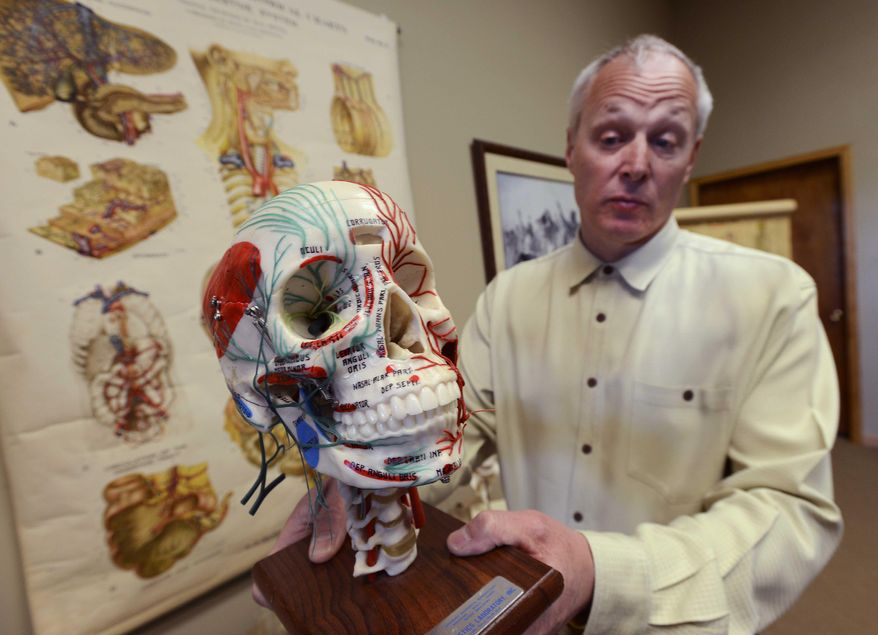 In this April 1, 2014 photo, Dr. Tom Pliura, head of the McLean County Medical Society, holds an anatomical skull in his office in LeRoy, Ill. A group of doctors in central Illinois is opening a cadaver dissection lab for high school students to give young people a head-start on future medical careers. The McLean County Medical Society is sponsoring the lab. It will be open to select students from advanced courses in subjects like anatomy and biology. (AP Photo/The Pantagraph, Steve Smedley)
