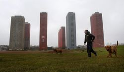 A man walks his dog near the 30-story Red Road apartment blocks which were built in the 1960s as modern replacements for slum housing in Glasgow, Scotland, Thursday, April 3, 2014. Organizers for the Commonwealth Games in Glasgow announced Thursday that the July 23 opening ceremony will include the live destruction of several high-rise buildings that dominate the Scottish city's skyline. (AP Photo/PA, Danny Lawson) UNITED KINGDOM OUT, NO SALES, NO ARCHIVE