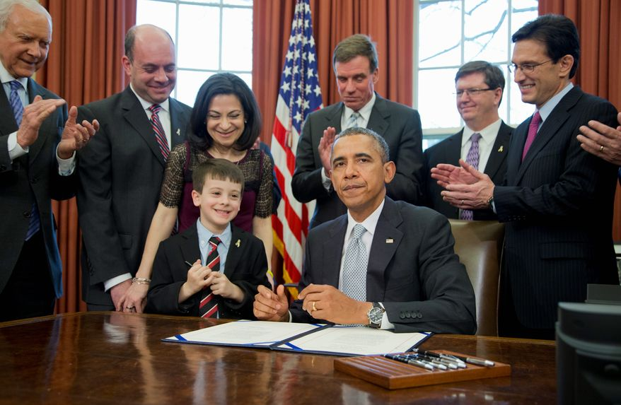 President Obama is joined at the White House by Mark Miller (back, second from left), Ellyn Miller, and son Jake Miller, who are applauded by Sen. Orrin G. Hatch, (back, left), Sen. Mark R. Warner, (fourth from left), Mike Gillette and Rep. Eric Cantor (right) after Mr. Obama signed into law a bill, the Gabriella Miller Kids First Research Act, on Thursday. (associated press)