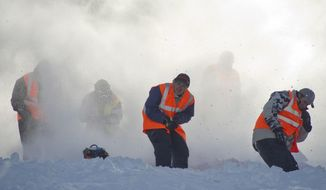 In this photo taken on March 22, 2014, hill helpers duck and cover as another sled spews snow, ice and maybe a little rock down the course at the World Championship Snowmobile Hill Climb in Jackson Hole,Wyo . The volunteers throw themselves into harms way to save riders and their machines from tumbling down the mountain. (AP Photo/Jackson Hole News & Guide, Price Chambers)