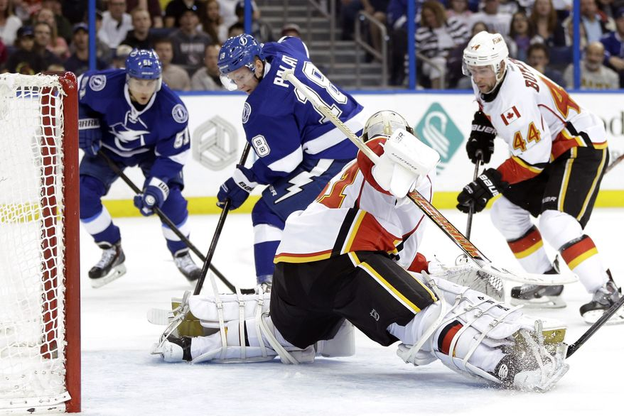 Tampa Bay Lightning left wing Ondrej Palat (18), of the Czech Republic, scores past Calgary Flames goalie Karri Ramo (31), of Finland, during the second period of an NHL hockey game on Thursday, April 3, 2014, in Tampa, Fla. Lightning's Valtteri Filppula (51), of Finland, and Flames' Chris Butler (44) look on. (AP Photo/Chris O'Meara)