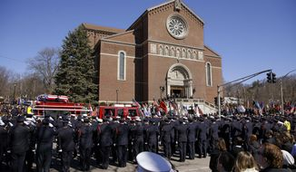 The funeral procession for Boston firefighter Michael R. Kennedy proceeds through saluting firefighters as it arrives at Holy Name Church in Boston, Thursday, April 3, 2014. Kennedy and Boston Fire Lt. Edward J. Walsh were killed Wednesday, March 26, 2014 when they were trapped in the basement of a burning brownstone during a nine-alarm blaze.(AP Photo/Stephan Savoia)