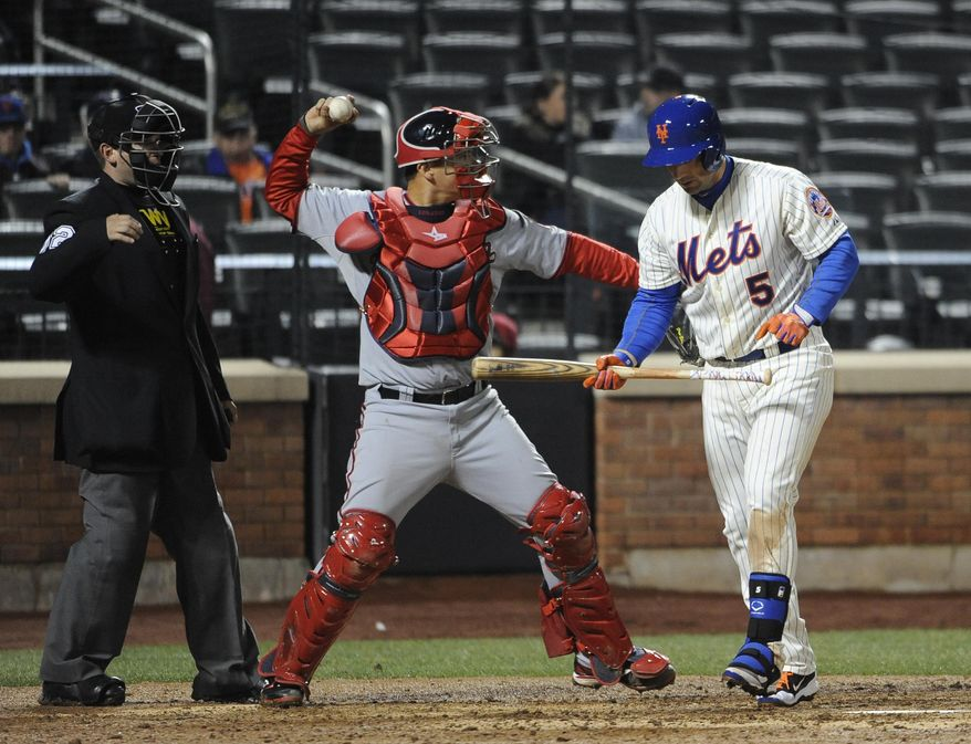 Washington Nationals catcher Jose Lobaton, center, throws the ball back to the mound after New York Mets' David Wright (5) struck out in the ninth inning of a baseball game at Citi Field on Wednesday, April 2, 2014, in New York. The Nationals won 5-1. (AP Photo/Kathy Kmonicek)