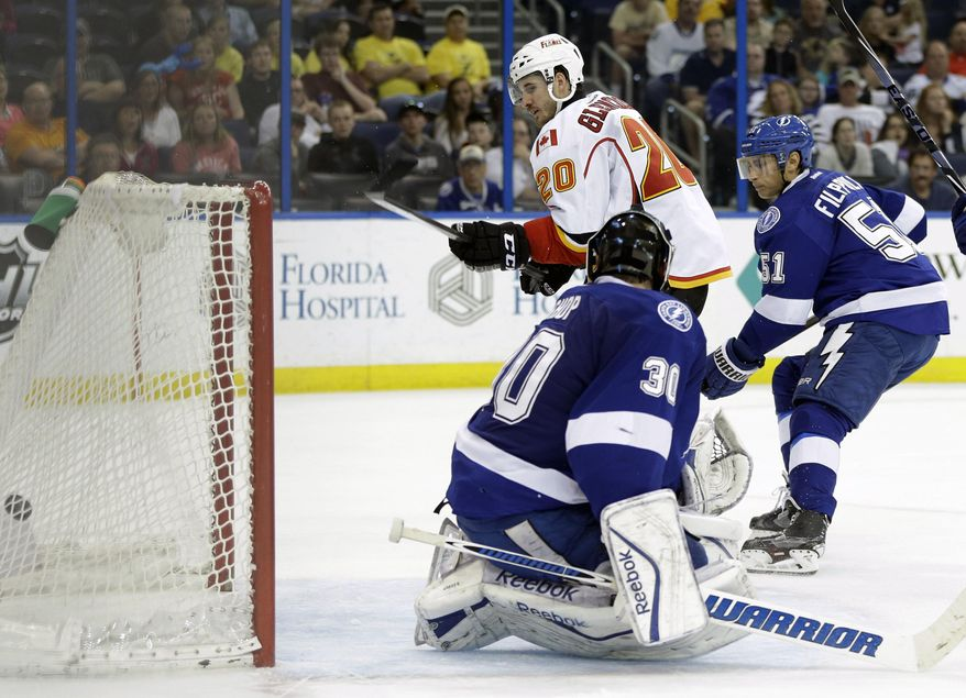 Calgary Flames left wing Curtis Glencross (20) slips the puck past Tampa Bay Lightning goalie Ben Bishop (30) for a goal during the third period of an NHL hockey game on Thursday, April 3, 2014, in Tampa, Fla. Lightning's Valtteri Filppula (51), of Finland, also defends. The Flames won the game 4-1. (AP Photo/Chris O'Meara)