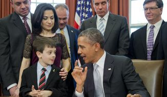 President Barack Obama talks to Jake Miller, left, accompanied by  Ellyn Miller, behind Jake, brother and mother of Gabriela Miller, before signing into law the H.R. 2019, the Gabriella Miller Kids First Research Act, in the Oval Office of the White House in Washington, Thursday, April 3, 2014.   (AP Photo/Manuel Balce Ceneta)