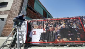 A worker hangs a fence scrim at Fenway Park in Boston, Thursday, April 3, 2014, during preparations for the Boston Red Sox's home-opener baseball game on Friday against the Milwaukee Brewers. The Red Sox will receive their World Series championship rings in a ceremony before the game to celebrate their third title in a decade. (AP Photo/Elise Amendola)