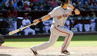 San Francisco Giants' Angel Pagan follows through on a three-run home run against the Arizona Diamondbacks during the eighth inning of an baseball game on Thursday, April 3, 2014, in Phoenix. (AP Photo/Matt York)