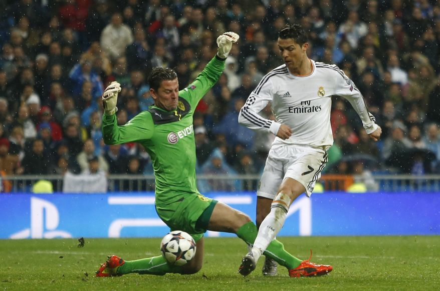 Real's Cristiano Ronaldo, right, scores his side's 3rd goal past Dortmund goalkeeper Roman Weidenfeller during a Champions League quarterfinal first leg soccer match between Real Madrid and Borussia Dortmund at the Santiago Bernabeu   stadium in Madrid, Spain, Wednesday, April 2, 2014. (AP Photo/Andres Kudacki)