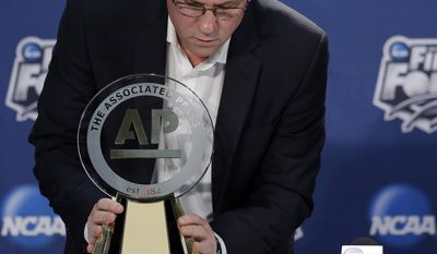 Wichita State's head coach Gregg Marshall looks at his trophy during a news conference Thursday, April 3, 2014, in Dallas. Marshall was named the AP College Basketball Coach of the Year. (AP Photo/David J. Phillip)