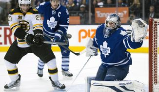 Toronto Maple Leafs goaltender James Reimer, right, prepares to make a glove save as Boston Bruins right winger Loui Eriksson (21) tries to deflect the shot while Leafs defenseman Dion Phaneuf (3) skates near during an overtime period of an NHL hockey game in Toronto on Thursday, April 3, 2014. (AP Photo/The Canadian Press, Frank Gunn)