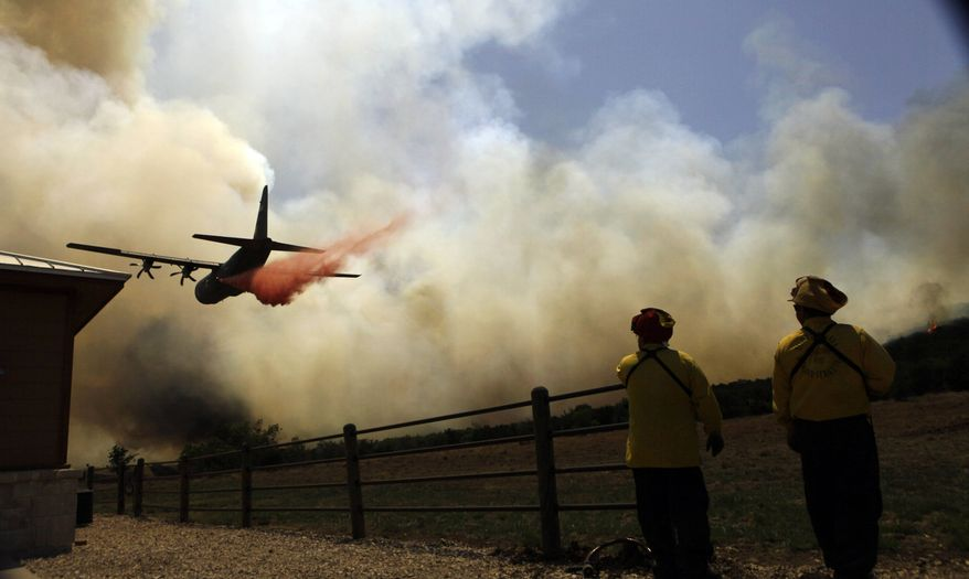 **FILE** Firefighters look on as an air tanker makes a pass over a wildfire near Possum Kingdom, Texas, on April 19, 2011. (Associated Press)