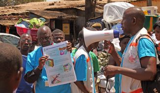 Health workers teach people about the Ebola virus and how to prevent infection in Conakry, Guinea. (AP Photo/Youssouf Bah)
