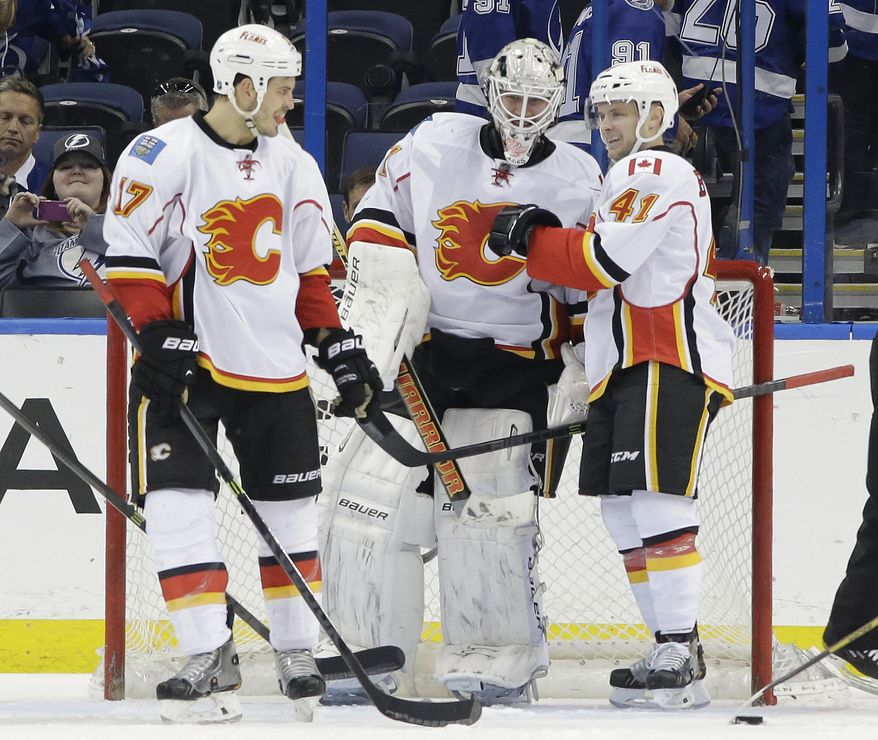 Calgary Flames goalie Karri Ramo, of Finland, center, celebrates with teammate Lance Bouma, left, and Chad Billins, right, after they defeated the Tampa Bay Lightning 4-1 during an NHL hockey game on Thursday, April 3, 2014, in Tampa, Fla. (AP Photo/Chris O'Meara)