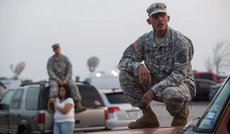 Staff Sgt. John Robertson, right, waits in a parking lot outside of the Fort Hood military base for updates about the shooting that occurred inside on Wednesday, April 2, 2014, in Fort Hood, Texas. (AP Photo/Tamir Kalifa)