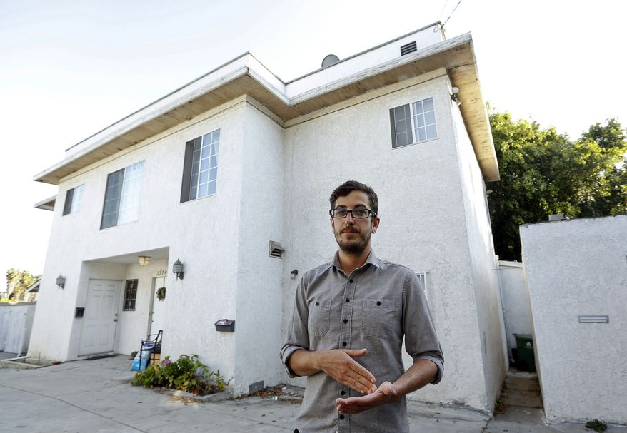 In this Thursday, March, 27, 2014 photo, Marc Caswell, who recently moved from San Francisco to Los Angeles, poses for a photo in front of his newly rented apartment in the Los Feliz district of Los Angeles. Rising rents in San Francisco compelled Marc Caswell to move to Los Angeles in September. (AP Photo/Damian Dovarganes)