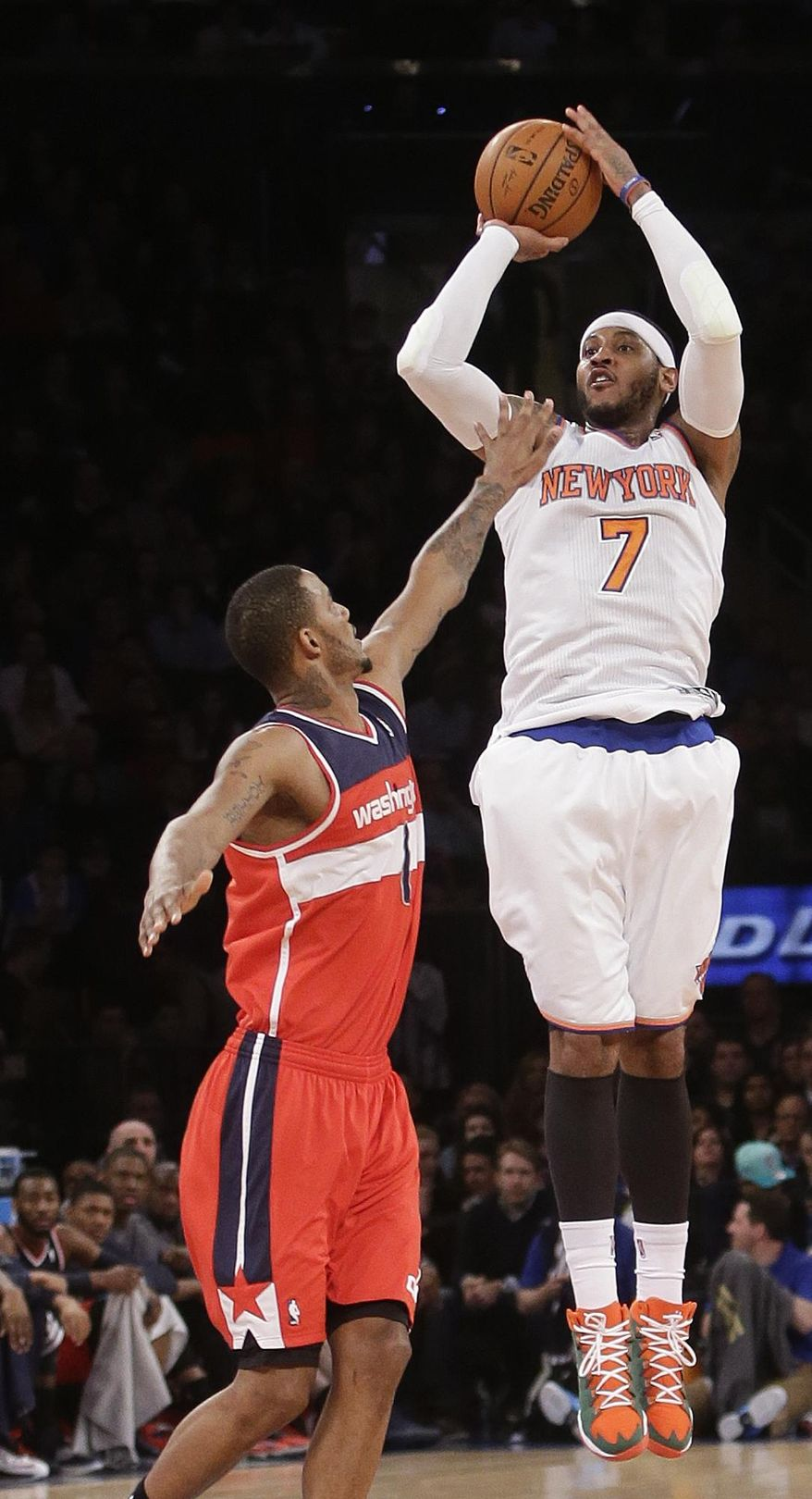 New York Knicks' Carmelo Anthony (7) shoots over Washington Wizards' Trevor Ariza (1) during the first half of an NBA basketball game Friday, April 4, 2014, in New York. (AP Photo/Frank Franklin II)