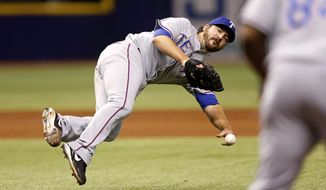 Texas Rangers pitcher Joe Saunders attempts a throw to first on a ball hit by Tampa Bay Rays' Yunel Escobar during the second inning of a baseball game Friday, April 4, 2014, in St. Petersburg, Fla. The throw went wide of first base and Escobar was awarded a single. (AP Photo/Mike Carlson)