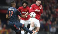Manchester United's Wayne Rooney, right, blocks a shot by Bayern's Jerome Boateng during the Champions League quarterfinal first leg soccer match between Manchester United and Bayern Munich at Old Trafford Stadium, Manchester, England, Tuesday, April 1, 2014.(AP Photo/Jon Super)