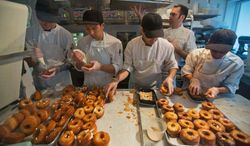 FILE- In this June 3, 2013 file photo, a baking crew makes Cronuts, a croissant-donut hybrid, at the Dominique Ansel Bakery in New York. Officials in New York City state that have closed the bakery dure to a severe mouse infestation. An NYC Department of Health spokeswoman says the rodent problem requires professional pest control but the bakery can reopen after inspectors determine the problem is fixed. (AP Photo/Richard Drew, File)