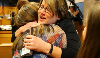 With her testimony over, a relieved Stacey Kalberman (center), former executive director of the state ethics commission, gets a hug from her friend Terri Cohen in her lawsuit at the Fulton County Courthouse on Thursday, April 3, 2014, in Atlanta. Closing arguments will start on Friday. Kalberman claims she was forced from her position as executive director of the state ethics commission after investigating Governor Nathan Deal's campaign.   (AP Photo/Atlanta Journal-Constitution, Curtis Compton)  MARIETTA DAILY OUT; GWINNETT DAILY POST OUT; LOCAL TV OUT; WXIA-TV OUT; WGCL-TV OUT