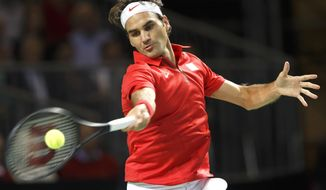 Roger Federer of Switzerland returns a ball to Mikhail Kukushkin of Kazakhstan during the second single match of the Davis Cup World Group Quarterfinal match between Switzerland and Kazakhstan, in Geneva, Switzerland, Friday, April 4, 2014. (AP Photo/Keystone, Salvatore Di Nolfi)