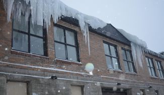 Large icicles hang from the back of a building in Houghton, Mich. on Friday, April 4, 2014.  A storm moving through the Great Lakes region has dumped a foot of snow on parts of Michigan's Upper Peninsula and could bring up to 17 inches. A storm moving through the Great Lakes region has dumped a foot of snow on parts of Michigan's Upper Peninsula and could bring up to 17 inches.  (AP Photo/Daily Mining Gazette, Kurt Hauglie)