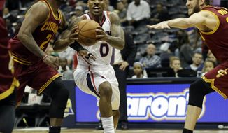 Atlanta Hawks' Jeff Teague, center, drives to the basket between the defense of Cleveland Cavaliers' Kyrie Irving, left, and Spencer Hawes in the first quarter of an NBA basketball game, Friday, April 4, 2014, in Atlanta. (AP Photo/David Goldman)