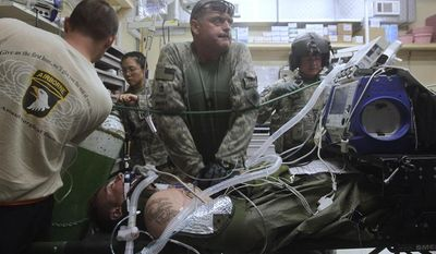**FILE** Sgt. Al Smoot, of Harold, Calif., part of a U.S. Medevac team, gives CPR to a U.S. soldier in the emergency room of the U.S. military hospital at Bagram Air Base, north of Kabul, Afghanistan, on June 7, 2009. (Associated Press)