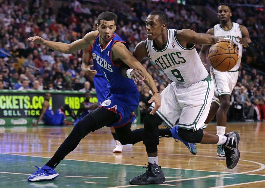 Philadelphia 76ers guard Michael Carter-Williams, left, tries to stop Boston Celtics guard Rajon Rondo on a drive to the basket during the second quarter of an NBA basketball game Friday, April 4, 2014, in Boston. (AP Photo/Charles Krupa)