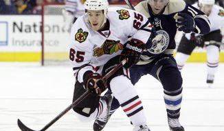 Chicago Blackhawks' Andrew Shaw, left, carries the puck across the blue line as Columbus Blue Jackets' Matt Calvert defends during the first period of an NHL hockey game on Friday, April 4, 2014, in Columbus, Ohio. (AP Photo/Jay LaPrete)