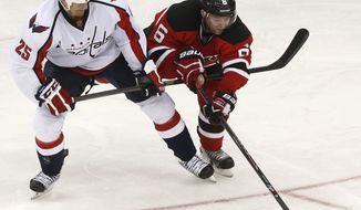 Washington Capitals left wing Jason Chimera (25) and New Jersey Devils defenseman Andy Greene (6) compete for the puck during the third period of an NHL hockey game, Friday, April 4, 2014, in Newark, N.J. The Devils won 2-1. (AP Photo/Julio Cortez)