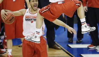 Wisconsin guard Traevon Jackson reacts as guard Ben Brust dunks the ball during practice for an NCAA Final Four tournament college basketball semifinal game Friday, April 4, 2014, in Dallas. Wisconsin plays Kentucky on Saturday, April 5, 2014. (AP Photo/Tony Gutierrez)